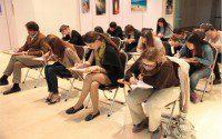 Участники старательно записывают текст за диктором
