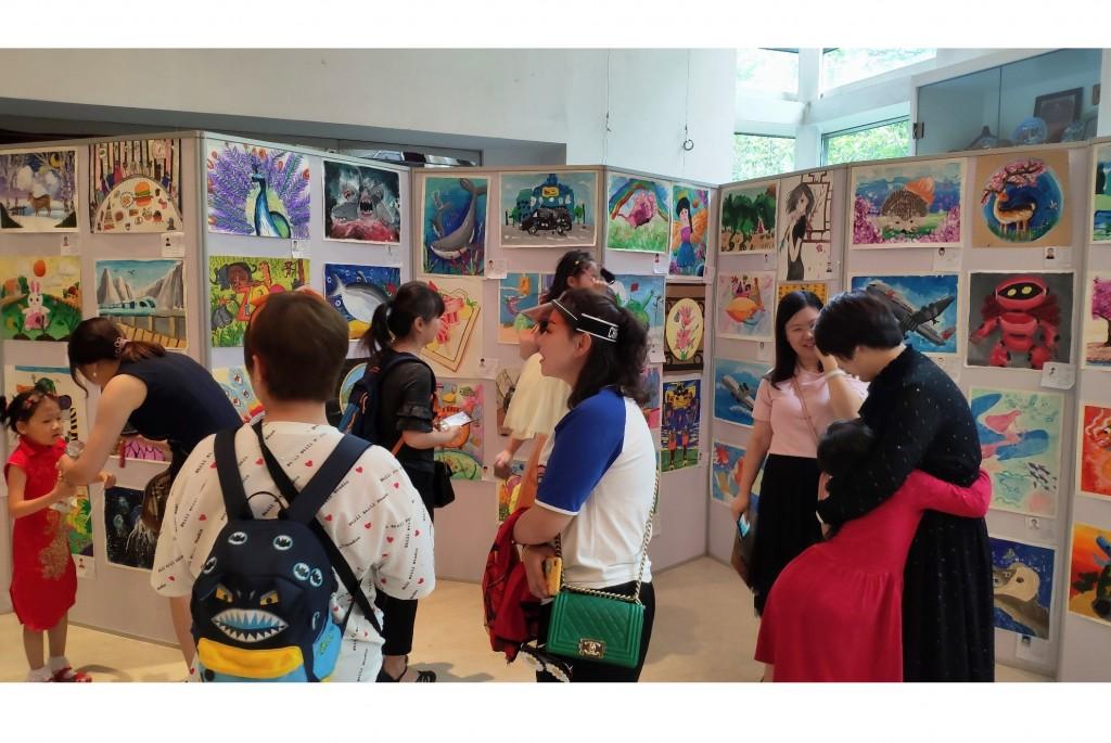 观众参观儿童绘画展 Посетители осматривают выставку детского рисунка