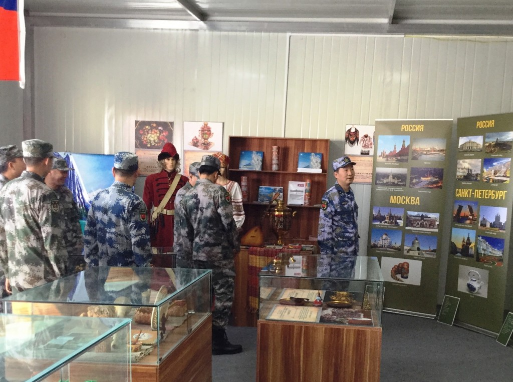 Заместитель начальника боевой подготовки войск НОАК контр-адмирал Ли Ханьцзюнь осматривает российский павильон