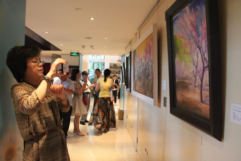 Посетители осматривают картины российских и китайских художников