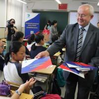 Виктор Коннов раздает ученикам учебные пособия и информацию о Российском культурном центре